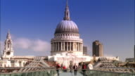 Wide shot pedestrains crossing Millenenium Footbridge over Thames with view of St. Paul's Cathedral/ London