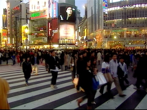 Wide shot pedestrians crossing street at busy Shibuya Crossing / Shibuya Ward, Tokyo, Japan