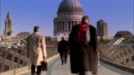 Wide shot pedestrians on Millenium Footbridge over Thames with view of St. Paul's Cathedral/ London