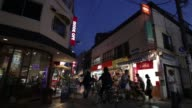 wide shot pedestrians walk past stores and restaurants at dusk in the Koenji district of Tokyo wide shot cyclists ride past pedestrians and stores at...