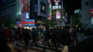Wide shot pedestrians walking across the street at Shibuya Crossing / Tokyo, Japan