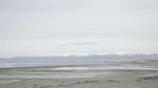 Wide shot, people paddle boarding in Great Salt Lake, wide shot