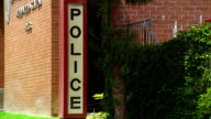 Wide shot 'police' sign on side of building with plants