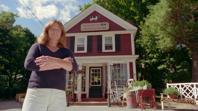 Wide shot portrait of small-town shopowner posing in front of store / Newfields, New Hampshire
