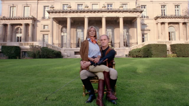 Wide shot portrait of wealthy equestrian couple sitting on chair in front of mansion (woman on man's lap)