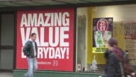 Wide shot Poundland store people walking past / People walking past window with poster 'Amazing Value Everyday' / Poundland sign above shop / Posters...