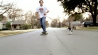 Wide shot pull out man on skateboard with beagle on leash pulling him down suburban street/ Dallas, Texas