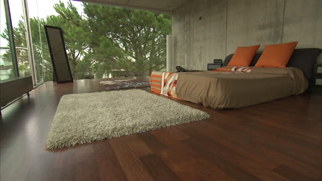 Wide Shot push-in - A shag rug covers the hardwood floor of a bedroom with a view of the outdoors. / Barcelona, Spain
