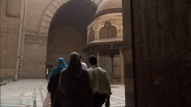 Wide Shot, push-in  - A small group of Muslim men and women walk through a corridor and out into the courtyard / Egypt