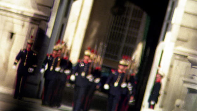 Wide shot rack focus from iron fence to palace guards marching / Madrid