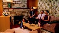 Wide shot REENACTMENT family watching TV in living room