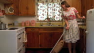 Wide shot REENACTMENT housewife smiling while vacuuming linoleum floor in kitchen