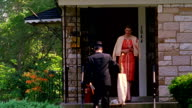Wide shot REENACTMENT vacuum salesman talks to woman on front porch of house