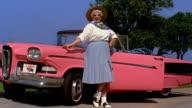 Wide shot REENACTMENT woman in poodle skirt posing beside pink 1958 Edsel Pacer convertible car