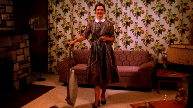 Wide shot REENACTMENT woman posing with vacuum cleaner in living room