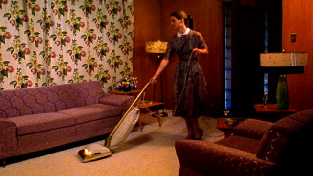 Wide shot REENACTMENT woman vacuuming living room, stopping and drinking from cocktail glass while smiling