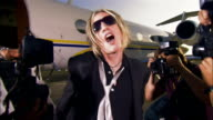 Wide shot Rock star posing and kicking toward paparazzi photographers then walks up steps and enters private airplane / Long Beach, California, USA