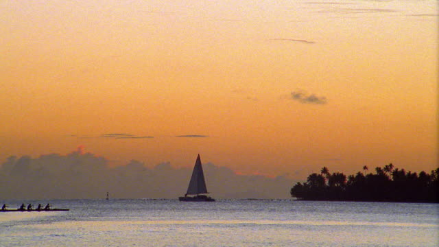 Wide shot sailboat on ocean with group rowing past in canoe at dusk / Bora Bora, French Polynesia