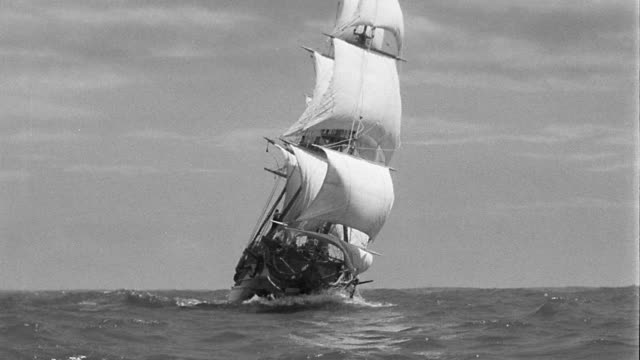 B/W wide shot sailing ship (model) coming towards + passing camera on choppy sea