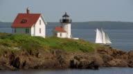 Wide shot schooner sailing past Curtis Island Lighthouse / Camden Harbor, Maine