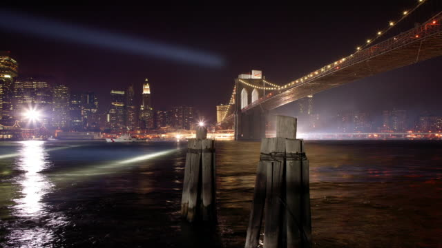 Wide shot Search lights flashing above Brooklyn Bridge at night/ New York City, New York, USA
