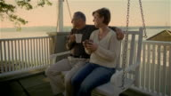 Wide shot senior couple sitting on porch swing drinking coffee / woman kissing man on cheek
