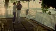 Wide shot senior couple slow dancing on deck