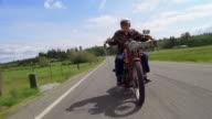 Wide shot Senior man riding motorcycle on country road / Washington, USA
