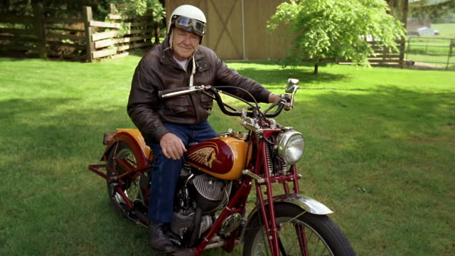 Wide shot Senior man sitting on motorcycle in backyard near shed / Washington, USA