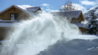 Wide shot senior man snowblowing in front of country house / Jackson Hole, Wyoming