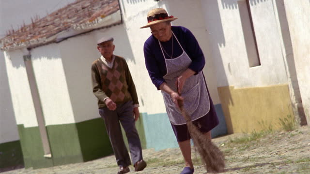 Wide shot senior woman sweeps dirt road as man walks up to her and they talk / Sao Pedro do Corval, Portugal