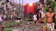 Wide shot shacks and people near railroad tracks / train approaching / Philippines