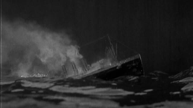Wide shot ship sinking in rough waters / STAGED