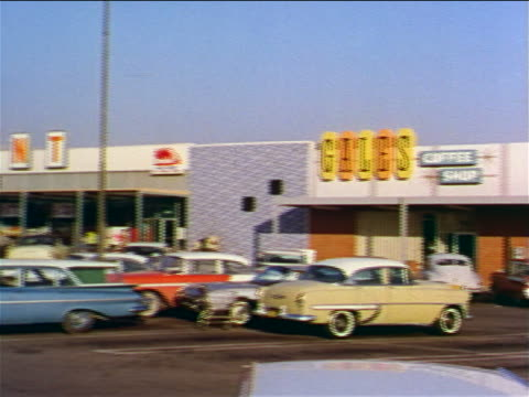 1962 wide shot PAN shopping mall with grocery store + parking lot / industrial