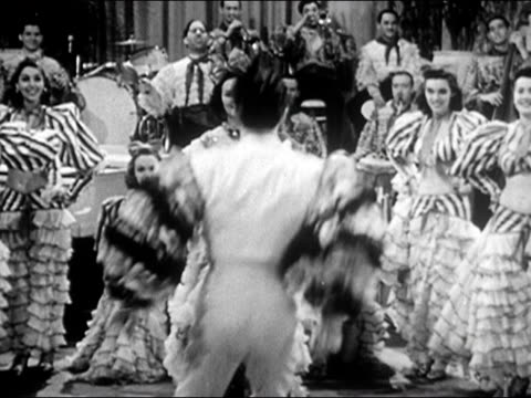 1941 Wide shot showgirls dancing as Latin big band plays in background/ zoom in medium shot man enters shot, knees and leans back as showgirl shimmies over him/ AUDIO