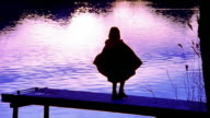 Wide shot silhouette of girl in cape walking and spinning on dock over lake / Fussen, Germany