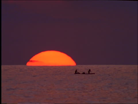wide shot silhoutte of 3 men rowing in small boat at sunset / Mexico