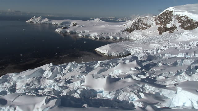 Wide shot Snowcapped glaciers floating on coast of Antarctic Sea/ Antarctica