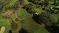 Wide shot soaring over golf course with bright green trees and grass