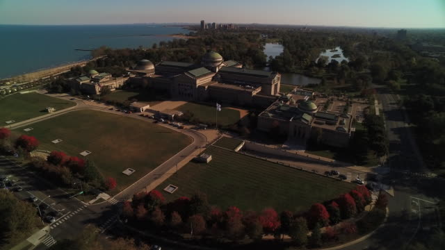 Wide shot soaring toward Chicago Museum of Science and Industry on bright autumn day
