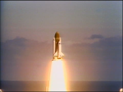1986 wide shot space shuttle Challenger blasting off from launch pad moving up into sky