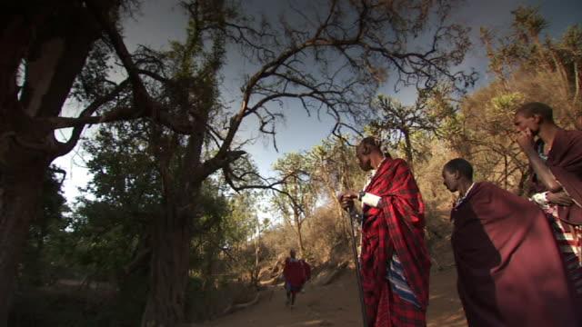 Wide Shot static - A Masai man runs a short distance before throwing his spear as his friends watch. / Masai Mara, Tanzania