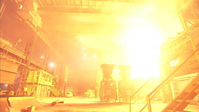 Wide Shot static - Huge billowing flames cast an orange glow throughout a steel mill / Claymont, Delaware