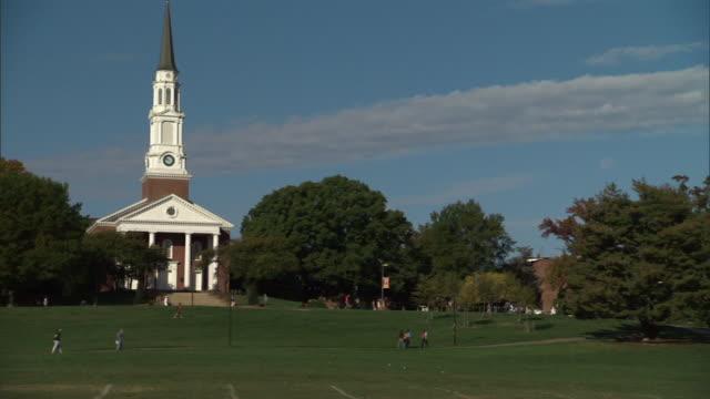 Wide Shot static - Pedestrians walk through a grassy park near a church. / Annapolis, Maryland, USA