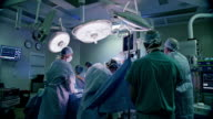 Wide shot, surgeons perform procedure in hospital operating room
