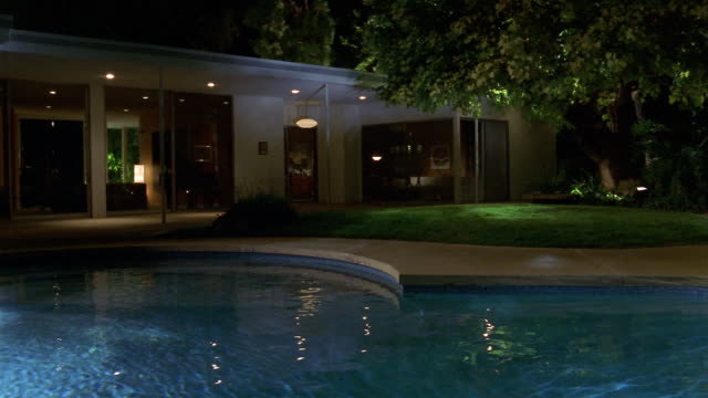 Wide shot swimming pool in backyard of midcentury modern for Modern house at night
