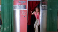 Wide shot teenage girl getting friend to join her in photo booth