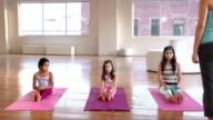 Wide shot three girls doing yoga in loft/ Brooklyn, New York