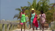 Wide shot Three mature women walking on beach and carrying body board and picnic baskets / Miami, Florida, USA