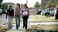 Wide shot three teenage girls walking down suburban street / talking and smiling